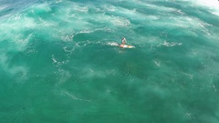 Aerial view of a man getting tubed while sup stand-up paddleboard surfing in Haw Stock Footage