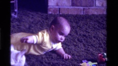 1975: a baby laying on it's stomach on the floor tries to play with a cat Stock Footage