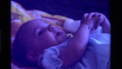 1975: a baby holding her bottle of milk laying down CALIFORNIA Stock Footage