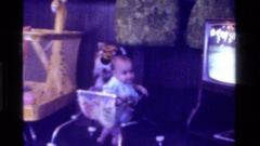 1975: baby scoots across the floor in an old walker while a game of golf plays Stock Footage