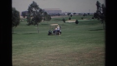 1976: one person is practicing his golf swing while another is sitting in a cart Stock Footage