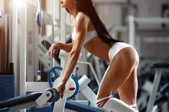 Beautiful young woman posing in the fitness gym Stock Photos