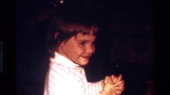 1977: a young girl smiles with her hands clasped in a living room CALIFORNIA Stock Footage