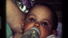 1977: a mother feeding her small baby with fluids from a feeding bottle Stock Footage