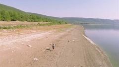 Aerial. One Man traveler goes on  coastline of  lake. Circular flight Stock Footage