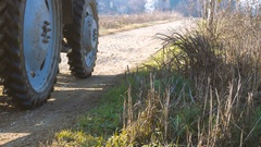 Farm tractor on a country road in the countryside Stock Footage
