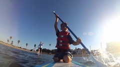 POV of a father, son and dog paddling an SUP stand-up paddleboard on a lake. Stock Footage