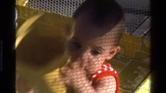 1977: baby in playpen playing with plastic container CALIFORNIA Stock Footage