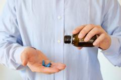 Man pouring some pills from a bottle Stock Photos