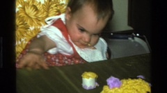 1977: baby reaches for piece of cake, takes a bite, smiles and drops frosting Stock Footage