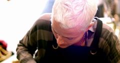 Craftswoman cutting leather belt Stock Footage