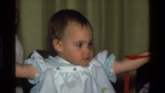 1977: baby in blue ruffled dress with ruffled pinafore, playing with ribbon Stock Footage