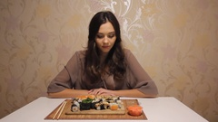 Young girl sitting at the table, tired of sushi and don't want eat it Stock Footage