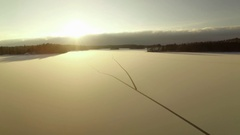 Long cracks on the ice cover of a frozen lake during sunset in Finland Stock Footage