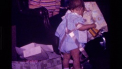 1977: baby playing with used wrapping paper CALIFORNIA Stock Footage