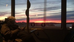 Old woman looks at sunset in afternoon - midwinter - Stockholm, from inside bus Stock Footage