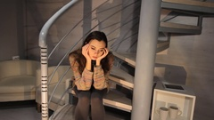 Young lonely sad girl is sitting at the spiral stairway in the home. Depressed Stock Footage