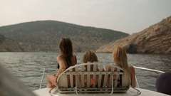 Three beautiful models in bikinis lying on a deckchair on the boat and looking Stock Footage