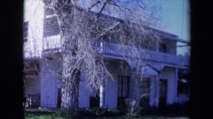 1969: leafless trees stand outside of white clapboard house with second floor Stock Footage