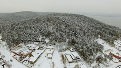 Aerial view of a village and forest and lake at winter Stock Footage