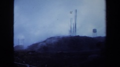 1971: clouds billow from large pipes sticking out of the ground on a high hill. Stock Footage