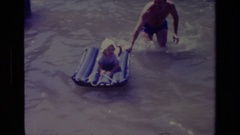 1978: father pushing infant child on inflatable raft on the river CANYON LAKE Stock Footage