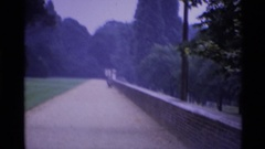 1969: people stand along a long path next to grass and trees LONDON ENGLAND Stock Footage
