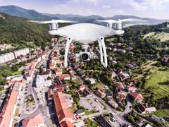 Hovering drone taking pictures of small town with hills, Slovaki Kuvituskuvat