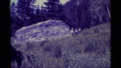 1975: a zooming in shot of a few people that are cautiously walking around Stock Footage
