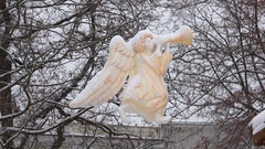 Angel statue silhouette hanging in heavy snow blizzard in christmas town Stock Footage