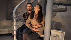 Young happy couple sitting on a staircase of a spiral stairway. Couple in their Stock Footage