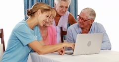 Female volunteer and senior citizens using laptop Stock Footage