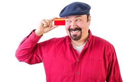 Gleeful man eyeing his credit card with a smile Stock Photos