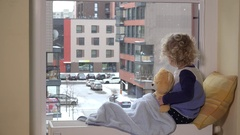 Sad toddler boy with best friend teddy bear looking at snow fall through window Stock Footage