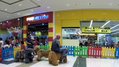Grandfather, grandson ride in electric animal in mall playhouse Stock Footage