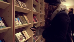 Young woman in a book store choose a book Stock Footage