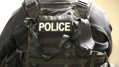Rear Shot of Police Swat Team Member's Flak Jacket Stock Footage