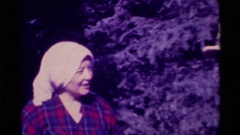 1975: a man wearing white cap talking to a woman standing near to orchard AGATE Stock Footage