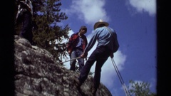 1975: a young man learning to rappel down a cliff, while his companions observe Stock Footage