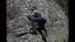 1975: an young lady in jeans attempts to climb a sheer rock face AGATE SPRINGS Stock Footage