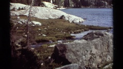 1975: lake with rocky shoreline and mountain with rock and fluffy clouds AGATE Stock Footage