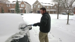 Man Wipes Snow Off Car - Dolly Shot Stock Footage