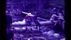 1975: a group of people cross a rivers by straddling and sliding along a log Stock Footage