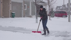 Woman Shovels Driveway During Snow Storm Stock Footage