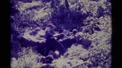 1975: man examining source of waterfall in difficult terrain on clear day AGATE Stock Footage