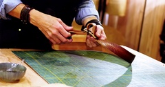 Mid section of craftswoman making leather belt Stock Footage