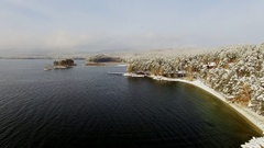 Copter flying over the lake and a forest at winter time Stock Footage