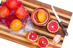 Whole and Sliced Ruby Red Grapefruit with Knife Stock Photos