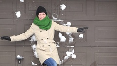 Woman standing near wall and someone throwing snow balls at her Stock Footage