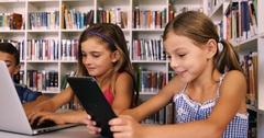 Schoolgirl using digital tablet in library Stock Footage